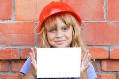 Muchacha sonriente del littl con el casco y la tarjeta blanca Imagen de archivo