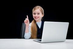 Muchacha sonriente del negocio que se sienta en la tabla con el ordenador portátil Foto de archivo