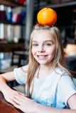Muchacha sonriente del niño con la naranja en la cabeza que se sienta en casa y mirada de la cámara Imágenes de archivo libres de regalías