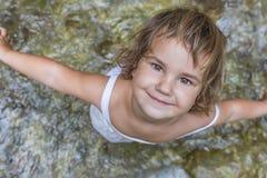 Muchacha sonriente del niño del niño en fondo de la cascada Fotos de archivo