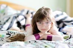 Muchacha sonriente del niño en la cama por mañana Fotografía de archivo