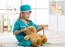 Muchacha sonriente del niño que finge ella es doctor en hospital imagen de archivo