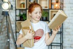 Muchacha sonriente del niño que lee un libro en clase El concepto de lifes Imagen de archivo libre de regalías
