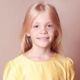Muchacha sonriente del niño que presenta en beige Foto de archivo libre de regalías