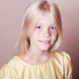 Muchacha sonriente del niño que presenta en beige Imagen de archivo libre de regalías