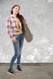 Muchacha sonriente del patinador que sostiene el monopatín Foto de archivo