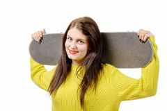 Muchacha sonriente del patinador que sostiene el monopatín en blanco Fotos de archivo libres de regalías