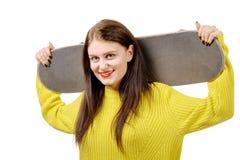Muchacha sonriente del patinador que sostiene el monopatín en blanco Imágenes de archivo libres de regalías