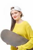 Muchacha sonriente del patinador que sostiene el monopatín en blanco Imagenes de archivo