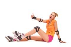 Muchacha sonriente del patinaje sobre ruedas que muestra el pulgar para arriba. Imágenes de archivo libres de regalías