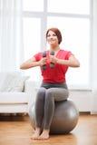Muchacha sonriente del pelirrojo que ejercita con la bola de la aptitud Fotos de archivo