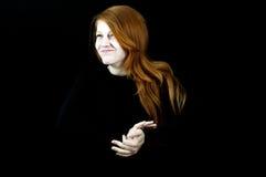 Muchacha sonriente del pelo rojo en negro Fotos de archivo