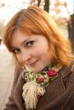 Muchacha sonriente del redhead en parque del otoño Fotos de archivo libres de regalías