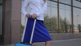 Muchacha sonriente del retrato en uniforme blanco-y-azul con la maleta en aeropuerto del fondo almacen de metraje de vídeo