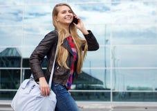 Muchacha sonriente del viaje con el bolso que habla en el teléfono móvil Imagen de archivo