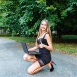 Muchacha sonriente del youg en vestido negro con el ordenador portátil que muestra el finger para arriba Fotos de archivo