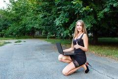 Muchacha sonriente del youg en vestido negro con el ordenador portátil que muestra el finger para arriba Fotografía de archivo