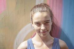 Muchacha sonriente delante de una pintada Imagen de archivo