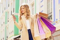 Muchacha sonriente elegante, hermosa del pelo rubio con compras usando su teléfono Compras felices Foto de archivo
