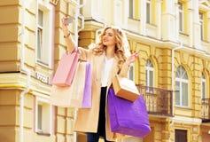 Muchacha sonriente elegante, hermosa del pelo rubio con las compras que toman el selfie en su teléfono Compras felices fotografía de archivo