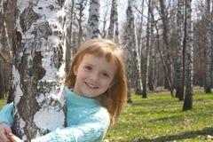 Muchacha sonriente en arboleda del abedul Imágenes de archivo libres de regalías