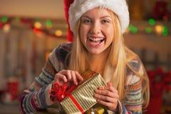 Muchacha sonriente en caja del regalo de Navidad de la abertura del sombrero de santa Imagenes de archivo
