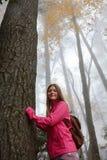 Muchacha sonriente en caminar viaje en bosque de niebla del otoño Imágenes de archivo libres de regalías