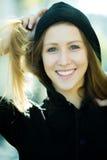 Muchacha sonriente en capilla negra Foto de archivo libre de regalías
