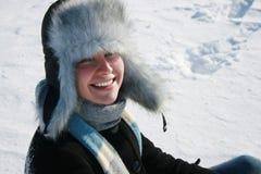 Muchacha sonriente en casquillo con las oído-solapas foto de archivo libre de regalías