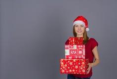 Muchacha sonriente en casquillo del invierno con los regalos de Navidad Fotos de archivo libres de regalías