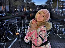 Muchacha sonriente en chaqueta rosada cerca del canal de Amsterdam en la tarde azul de la hora entre las bicis Foto de archivo