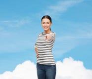Muchacha sonriente en clother casual que señala en usted Imagenes de archivo