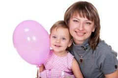 Muchacha sonriente en color de rosa y su mama Imagenes de archivo