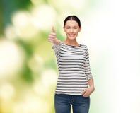 Muchacha sonriente en el clother casual que muestra los pulgares para arriba Fotos de archivo libres de regalías