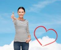 Muchacha sonriente en el clother casual que muestra los pulgares para arriba Imagen de archivo libre de regalías
