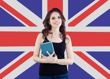 Muchacha sonriente en el fondo BRITÁNICO de la bandera Mujer alegre bonita que aprende lengua inglesa y que viaja en Reino Unido imagen de archivo libre de regalías
