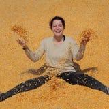 Muchacha sonriente en el montón del maíz después de la cosecha fotografía de archivo