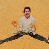 Muchacha sonriente en el montón del maíz después de la cosecha imagen de archivo libre de regalías