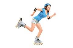 Muchacha sonriente en el patinaje de rodillos Imágenes de archivo libres de regalías