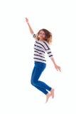 Muchacha sonriente en el salto en blanco blanco de la camiseta Foto de archivo libre de regalías