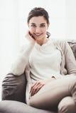 Muchacha sonriente en el sofá Imagenes de archivo