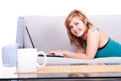 Muchacha sonriente en el sofá con la computadora portátil Imagen de archivo