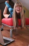 Muchacha sonriente en el sofá rojo Foto de archivo