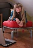 Muchacha sonriente en el sofá rojo Imagen de archivo