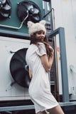 Muchacha sonriente en el sombrero blanco del vestido y de piel en ciudad Foto de archivo libre de regalías