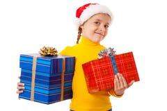 Muchacha sonriente en el sombrero de Santa con dos rectángulos de regalo Fotografía de archivo