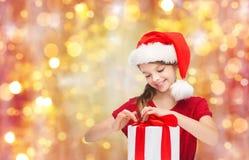 Muchacha sonriente en el sombrero de santa con el regalo de la Navidad Fotos de archivo libres de regalías