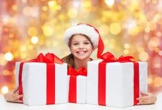 Muchacha sonriente en el sombrero de santa con los regalos de la Navidad Fotos de archivo