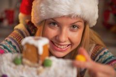 Muchacha sonriente en el sombrero de santa que adorna la casa de la galleta de la Navidad Fotografía de archivo