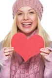 Muchacha sonriente en el sombrero del invierno que muestra la postal en forma de corazón Fotografía de archivo